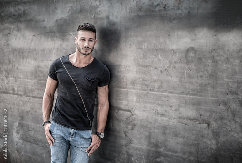 Poster Handsome young man standing against concrete wall, looking at camera, wearing black t-shirt and jeans