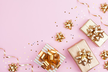Fashion gifts or presents boxes with golden bows and star confetti on pink pastel background top view. Flat lay composition for birthday, christmas or wedding.
