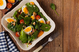 Delicious salad of fresh spinach, boiled egg, tomatoes, nuts and sunflower seeds - 232652228