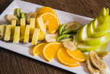 sliced fruits in a white plate are on the table - proper nutrition, raw foods, vegetarianism, pineapple, apple, orange, banana and kiwi