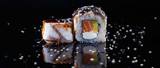 delicious sushi roll with fish and sesame poured with soy sauce on a black background with reflection © Natalya