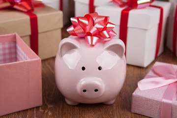 pink piggy bank with red bow against the background of gift boxes