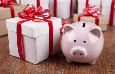 pink piggy bank with gift boxes with red bows