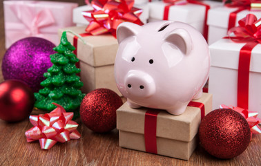 pink piggy bank with gift boxes and Christmas toys close up