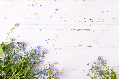 Frame from  blue forget-me-nots or myosotis flowers on  white wooden background.