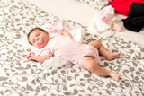 A cute baby girl lying and sleeping on a grey patterned blanket with a dummy in her mouth. - 232695673