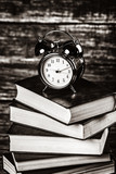 vintage alarm clock and books on wooden background. Image in white and black color style. - 232695696