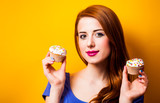 Redhead woman in blue dress with cupcakes on yellow background isolated - 232696082