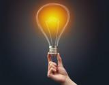 Hand holding light bulb on dark background. New idea concept - 232699076