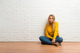 Young girl sitting on the floor with sad and depressed expression. Serious gesture - 232700204