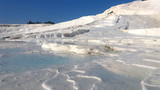 Beautiful blue thermal pools surrounded by white hills at Pamukkale, Denizli with bright blue skies at background. - 232700213