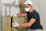 Worker in protective respirator mask insulating rock wool insulation in wooden frame for future house walls for cold barrier. Comfortable warm home, economy, construction and renovation concept - 232700299