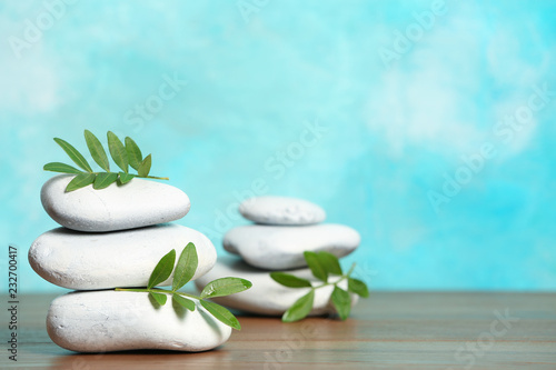 Leinwanddruck Bild Spa stones and bamboo leaves on table against color background. Space for text