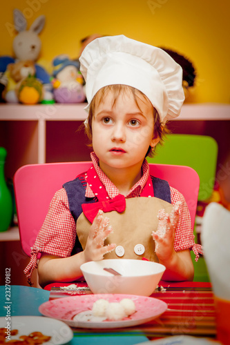 Wall mural Cooking concept. Sweet little cute child girl is learning how to make a cake in the home kitchen.