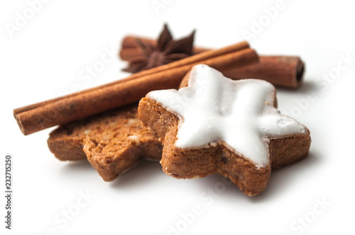 Leinwandbild Motiv closeup of christmas biscuit shaped star with anise flower and cinnamon stick on white background