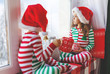 children girl and boy is sad on Christmas morning by the window