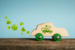 Concept of eco car. Wooden toy car with leaves and electric plug symbols impressed on the side.