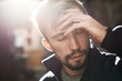 closeup portrait of a young bearded crying man in warm fleece sweater. man is standing in a beautiful backlight on the street with closed eyes and tear on cheek . man looks very upset and sad