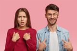 Indoor shot of indignant Caucasian young woman and man point at themselves, have discontent facial expressions, dressed in fashionable clothes, isolated over pink background. So, why are we? - 232731401