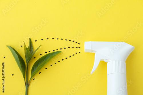 Leinwandbild Motiv Closeup of white spray  bottle on yellow background with spraying line from black saseme seeds to baby plant, Spraying water or planting concept