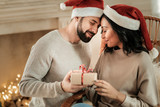 Happy relationships. Joyful positive young people wearing Santa hats and smiling to each other while celebrating Christmas together - 232736019