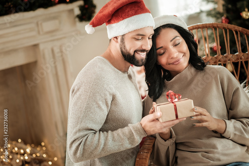 Foto Murales Christmas gifts. Nice happy young couple being together and looking at the gift while celebrating Christmas