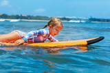 Happy baby girl - young surfer paddle on surfboard with fun on sea waves. Active family lifestyle, kids outdoor water sport lessons and swimming activity in surf camp. Beach summer vacation with child - 232743401