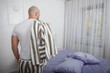 Young handsome bald bearded man in striped gray pajamas and white T-shirt undresses before going to bed.