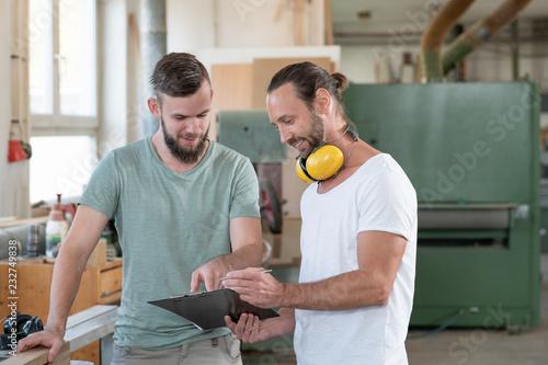 Leinwanddruck Bild two worker in a carpenter's workshop