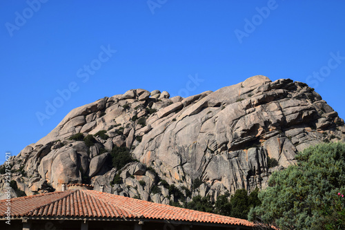 round and smooth granite formation in the foreground a roof covered with red tiles, rocky granitic massif landscape impressions in north sardinia in autumn as a rock background