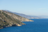 Summer time in Greece. Beautiful Greek coastline next to sea shore during warm weather.