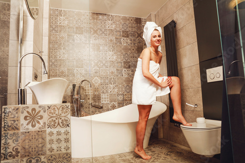 Leinwanddruck Bild slim young woman in bathroom and white towel