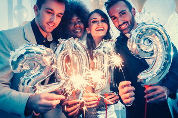 Group of party people celebrating the arrival of 2019, men and women looking into camera © Kzenon