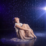 Girl sitting in the rain, night concept.