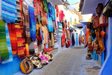 Moroccan handmade crafts, carpets and bags hanging in the narrow street of Essaouira in Morocco with selective focus - 232794416