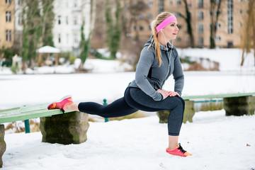 Frau beim Stretching während des Sport Trainings im Winter