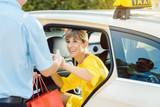 Taxifahrer hilft Frau beim Aussteigen aus dem Taxi - 232802827