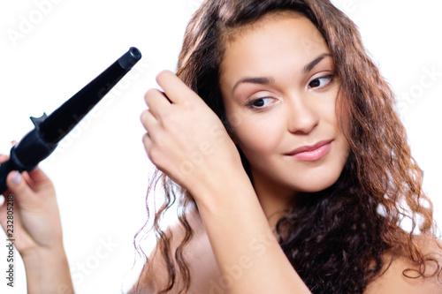 Leinwanddruck Bild Brunette curling her hair