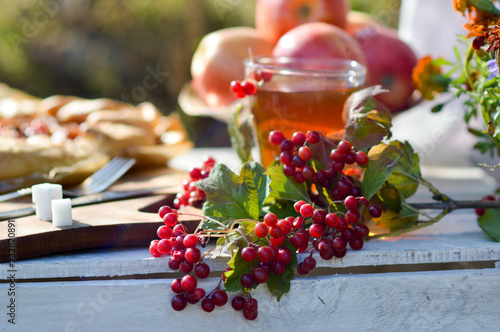 Foto Murales tea with kalina as a remedy for colds. Warming tea with viburnum and apple on a wooden table
