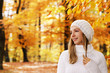 Attractive woman withscarf and cap lokking sideways in autumnal nature
