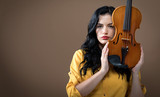 Young woman with a violin on a brown background - 232826070
