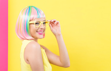 Young woman in a colorful wig with sunglasses on a split yellow and pink background © Tierney
