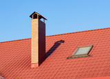 Brick chimney with skylight on the terracotta rooftop, closeup