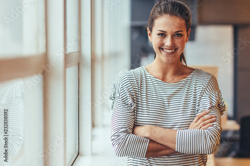 fototapeta na ścianę Smiling businesswoman standing with crossed arms