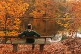 Mann sitzt auf einer Bank am Fluss in romantischer Herbst Landschaft, Konzept Auszeit, Balance, Erholung