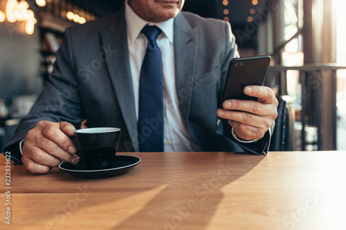 Foto Murales Smart phone in hand of a senior businessman at cafe