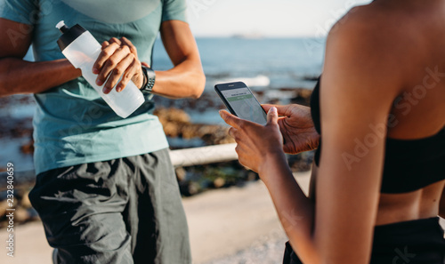 Leinwanddruck Bild Couple relaxing after workout outdoors