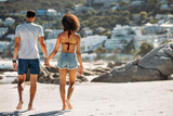 Tourist couple walking on beach on a sunny day