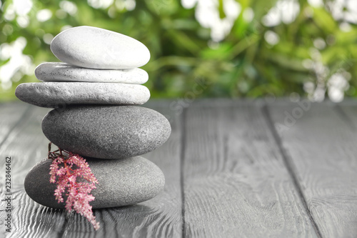 Leinwanddruck Bild Spa stones on table against blurred background. Space for text