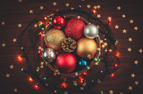 A small basket full of Christmas decorations, balls, a cone with glowing garland and golden stars confetti - 232850835